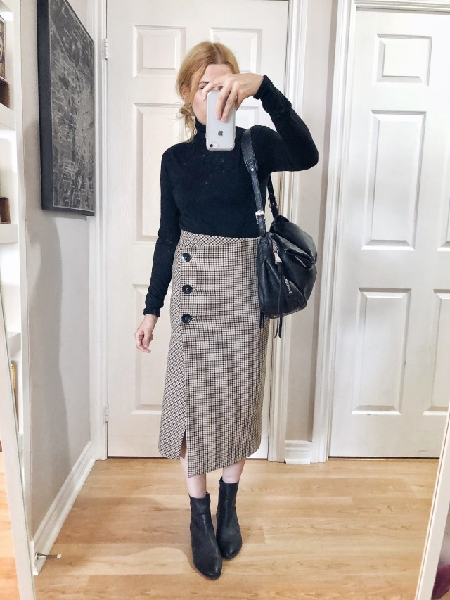 I am wearing a black knit turtleneck, plaid midi pencil skirt, and black boots.