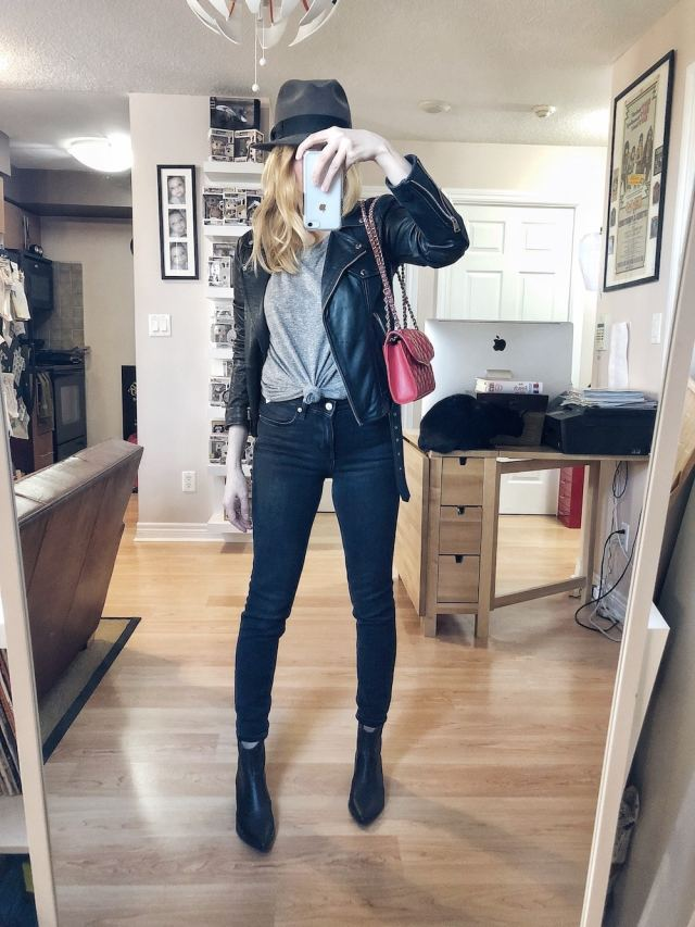 I am wearing A knotted, grey t-shirt, black skinny jeans, a leather moto jacket, a vintage fedora, black booties, and a red purse.
