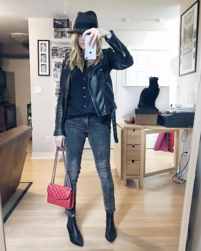 I am Wearing a black silk blouse from Everlane, skinny grey jeans, black Steve Madden Booties, a Red quilted leather purse, and a vintage fedora.