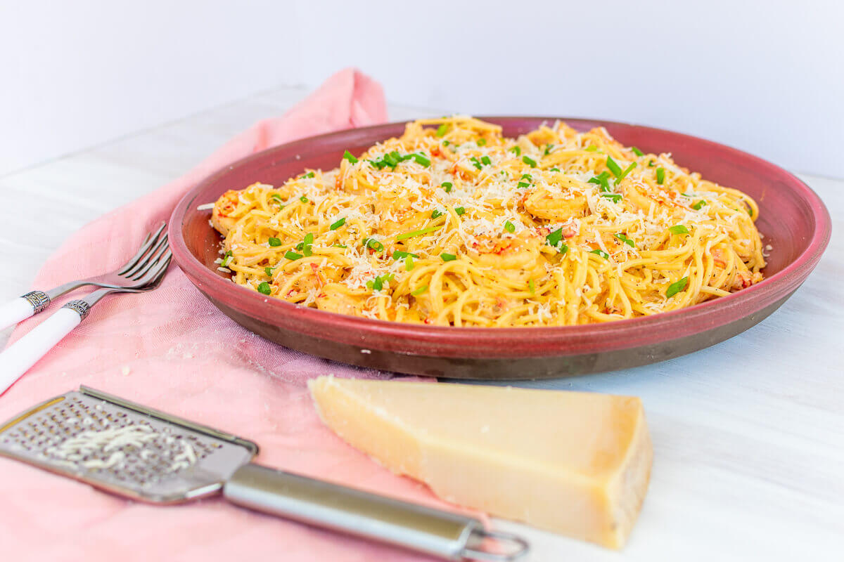 Big shallow pink plate of creamy shrimp pasta with Parmesan cheese on the side, utensils, cheese grater, and a pink cloth.