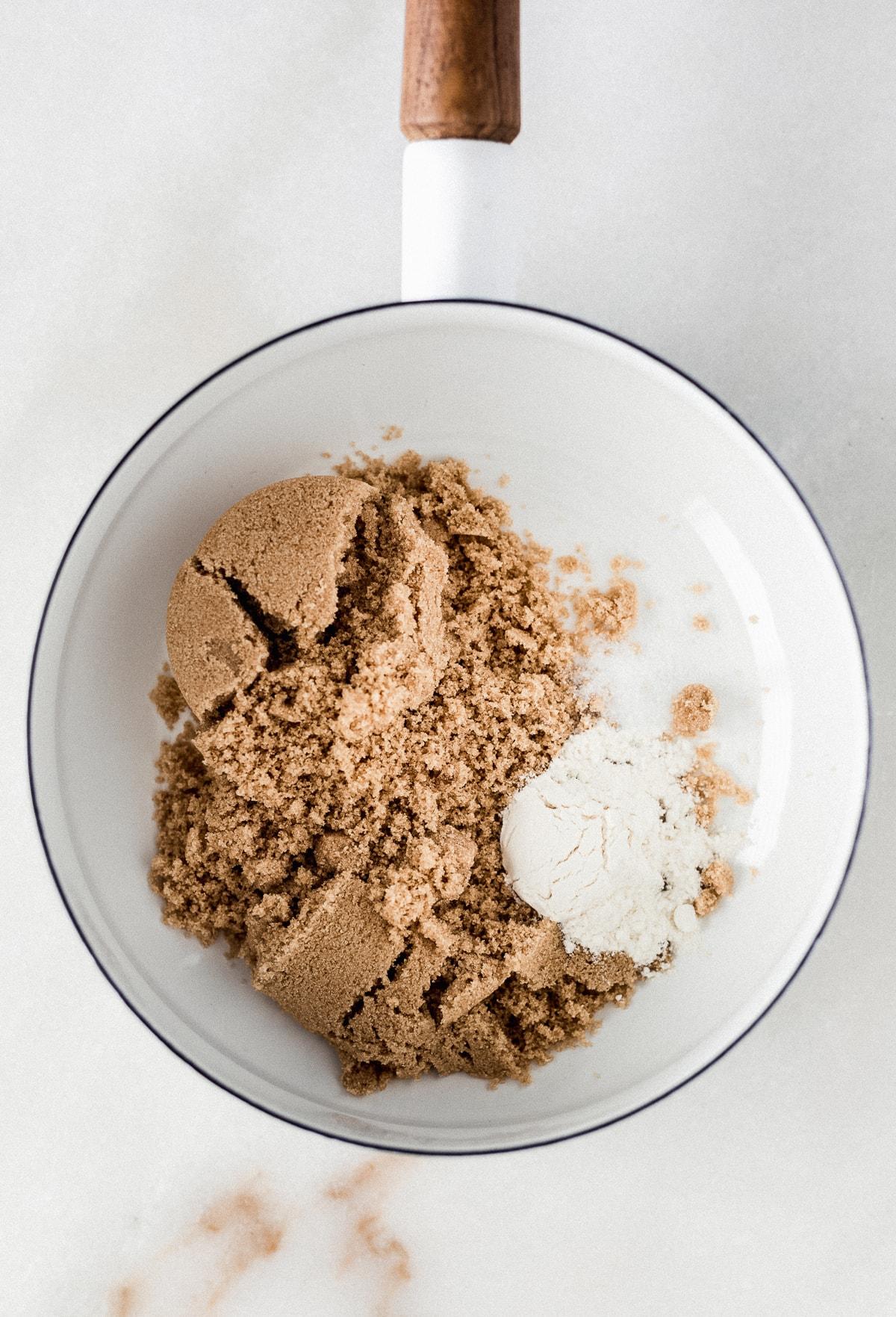 overhead view of brown sugar, flour and salt in a white saucepan.
