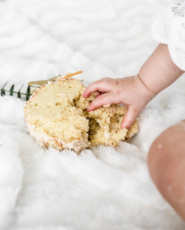 baby hand grabbing a smashed vanilla cake.