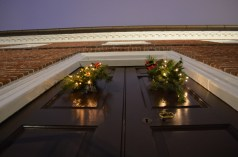 Holiday swags with modern lights on Kenmore's doors.