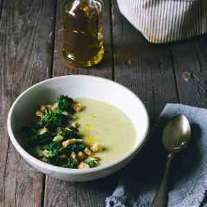 potatis soppa på ett bord brevid flaska av rapsolja