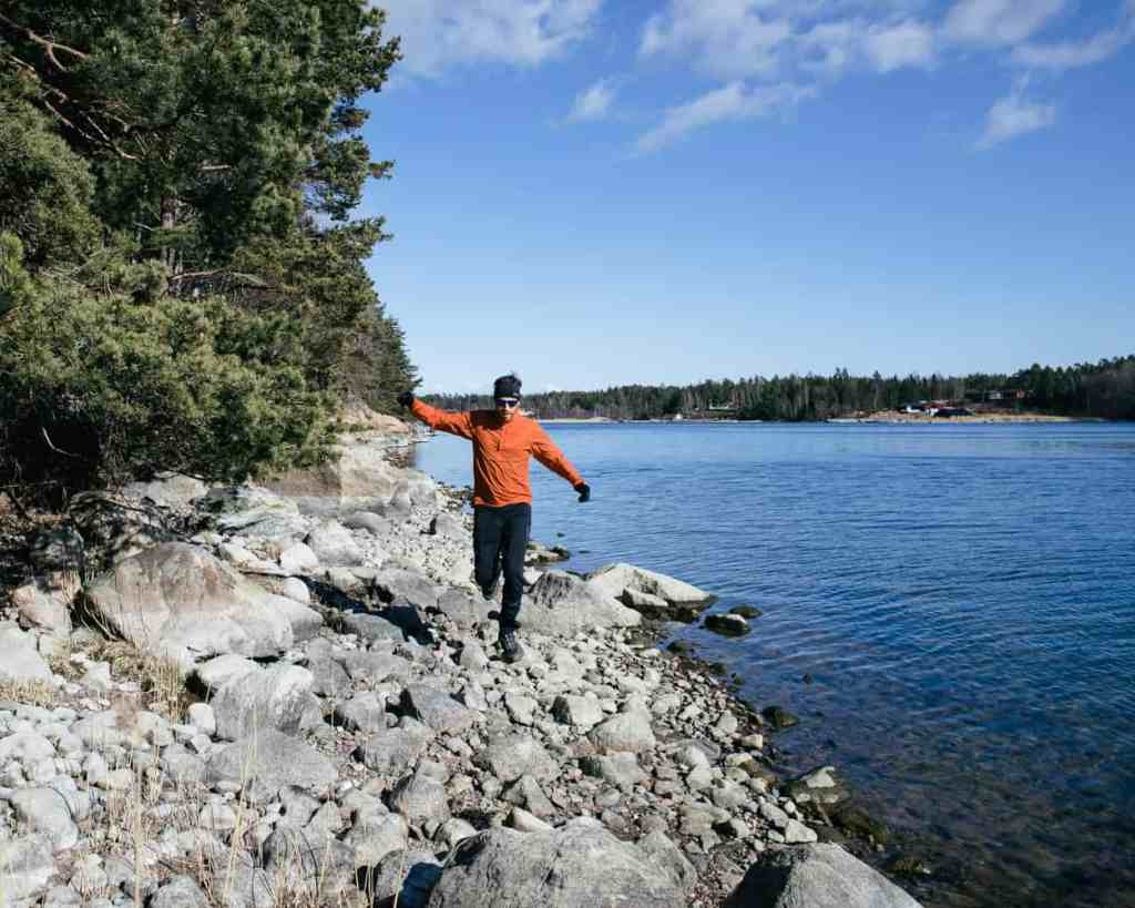 Man running along a rocky coastline in Sweden.