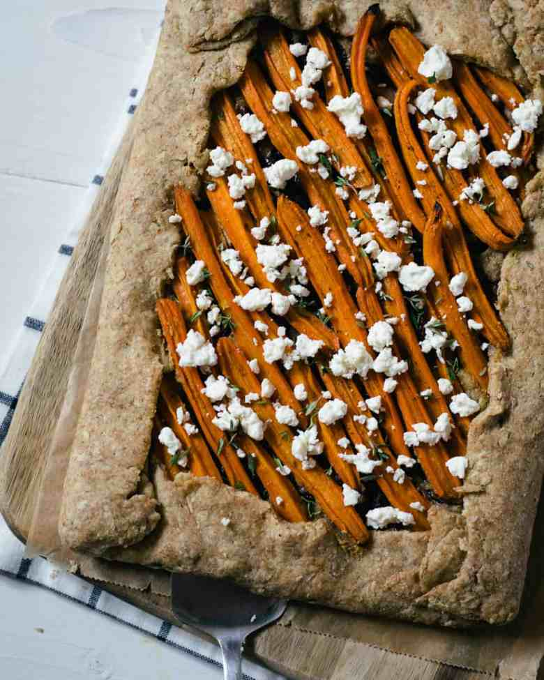 A carrot galette with feta cheese on a cutting board