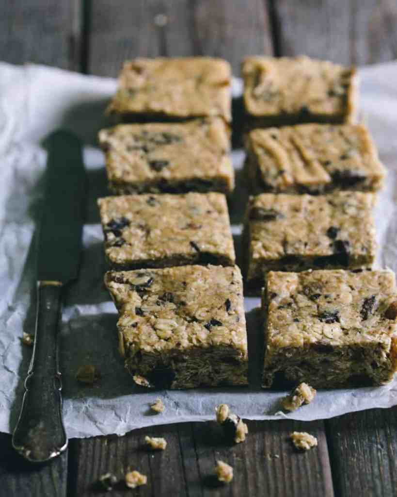 Granola bar squares on a wooden table with a knife.
