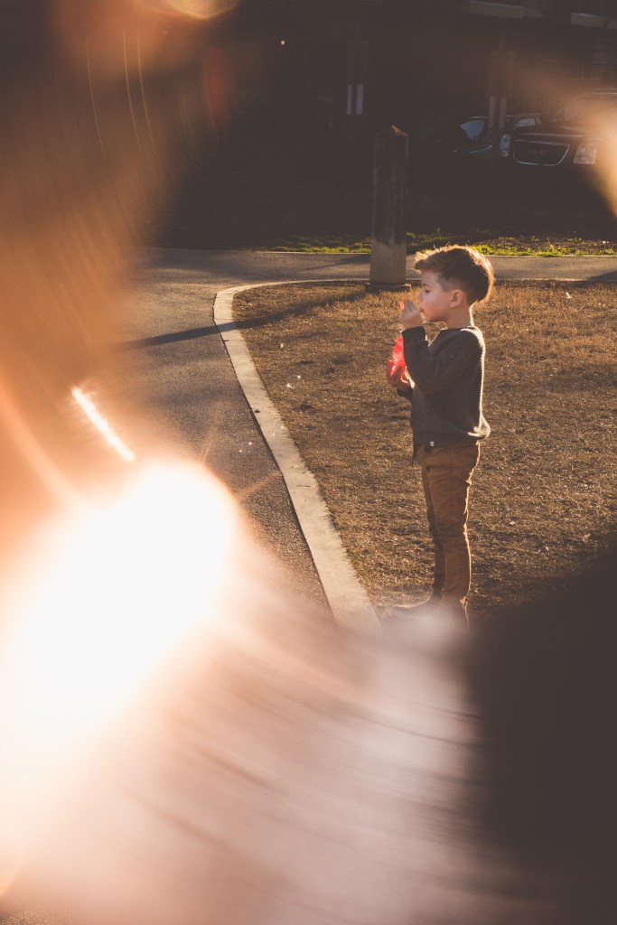 Image of boy blowing bubbles inside a ring of fire photo