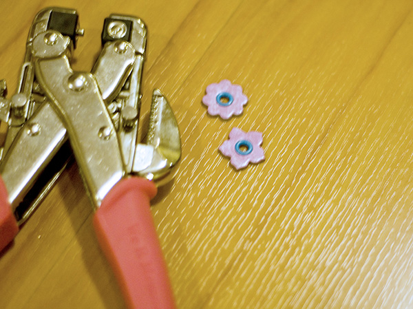 Step 7 - Attach eyelets to chipboard flowers using the ever-reliable, handy-dandy Cropadile!