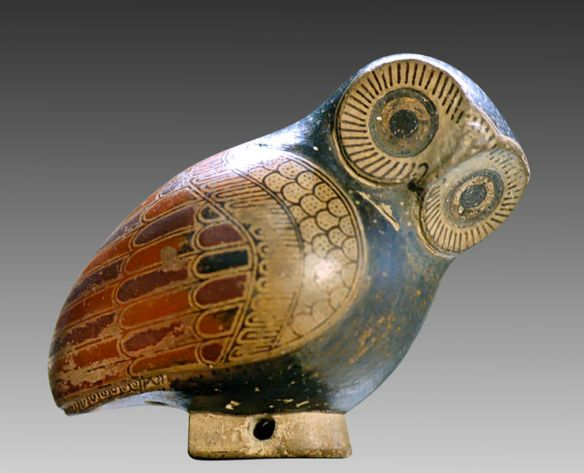 Detta är en parfym-uggla i keramik. Den lutar sig framåt och lägger sitt uttrycksfulla huvud på sned.