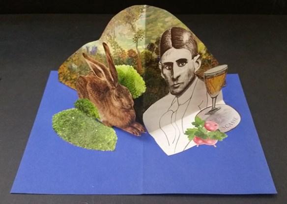Fotografi som visar ett blått kort. Från kortets bas står en grönskande fond och framför den finns bilder på en hare, en man och ett glas vin.
