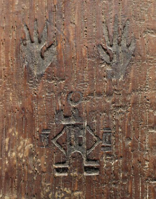 Närbild av en detalj på en träpanels baksida. Bilden visar en brännmärkning av ett signum, som tillhörde en viss panelmakare.