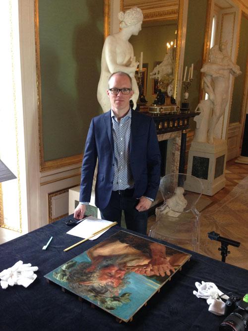 Fotografi som visar geologen Johannes Edvardsson, med inriktning dendrokronologi. Han står i en slottslik interiör med en oljemålning framför sig på ett bord.