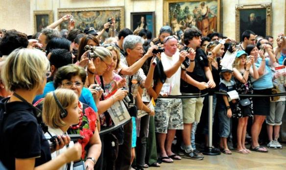 Ivriga besökare på konstmuseet Louvren fotograferar målningen MonaLisa.