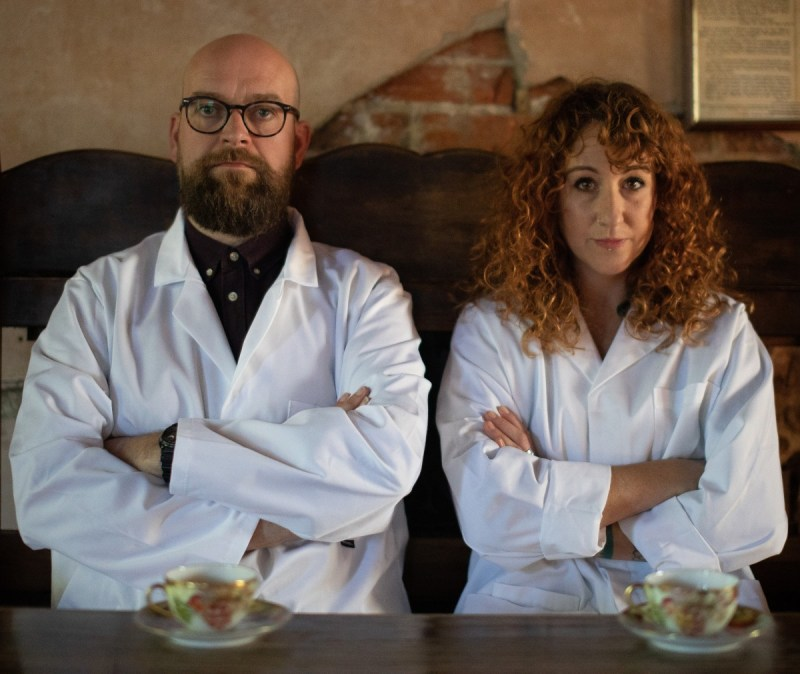 The Story Scientists (Findlay Napier and Megan Henwood) sat on a bench wearing lab coats with their arms crossed, looking serious. They have cups of tea in china cups and saucers on the table in front of them.