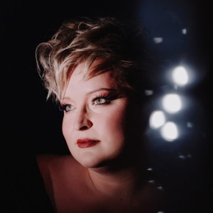 Mel Biggs looking very glamorous with short hair and make-up on. The background is dark with some lights twinkling in the distance.