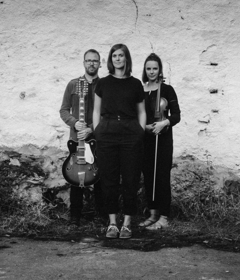 Black and white photo of Salt House stood in front of a wall. Ewan is holding a guitar and Lauren a fiddle. Jenny is stood just in front of them and they're all looking ahead at the camera.