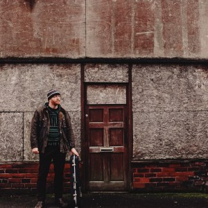 Tom Kitching stood outside a boarded up building. He has a fiddle in a case, and is wrapped up warm in a coat and woolly hat.