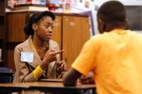 Fresno State Interpreting intern, Sophie Powell, signs to Buchanan High student, Emmanuel Akande. Photo Credit: Cary Edmondson, Fresno State Magazine