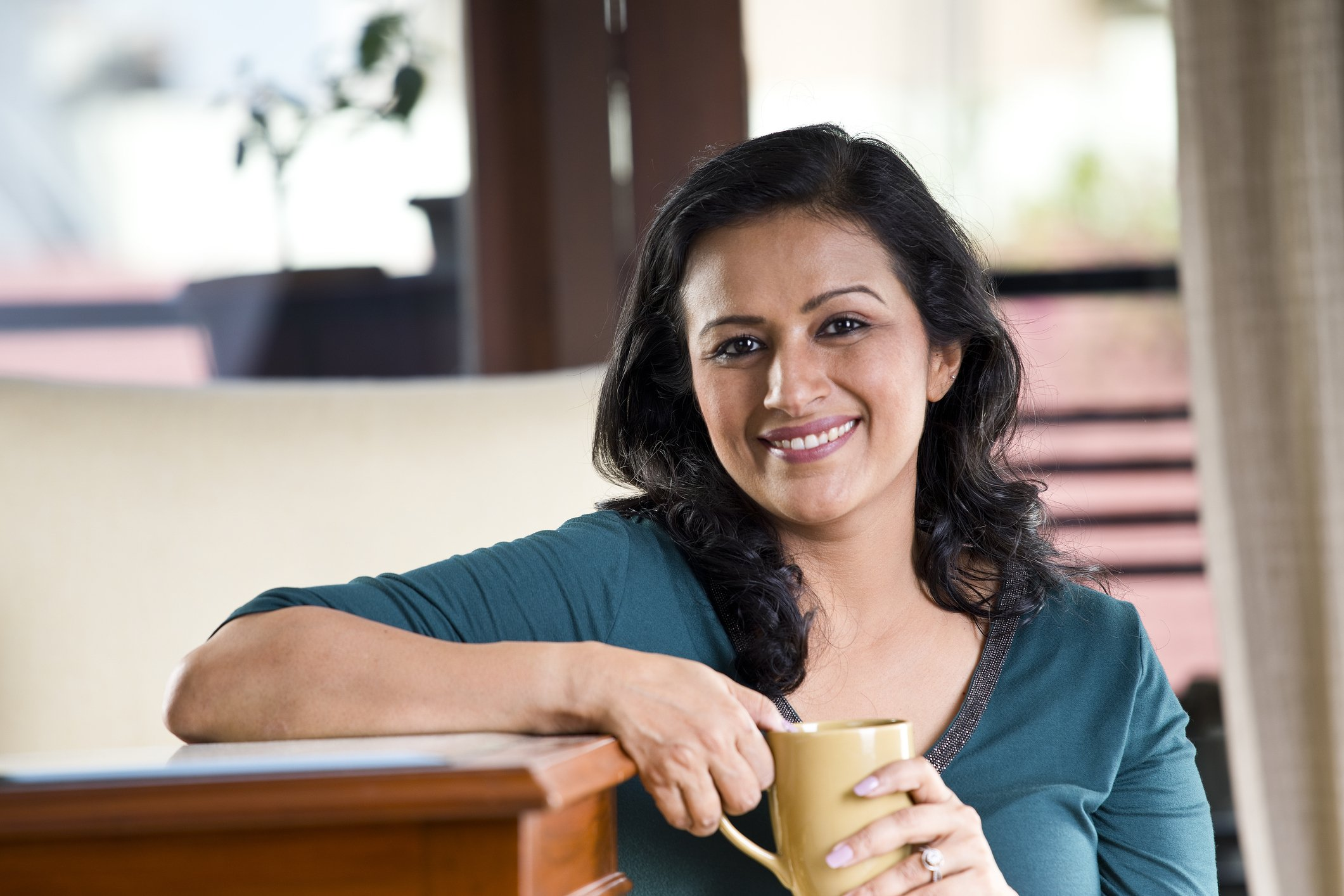 Beautiful Indian woman drinking coffee at home
