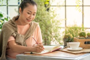 Asian senior woman relaxing with writing diary in greenhouse garden
