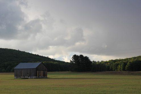 Dechow barn in field below stormy sky