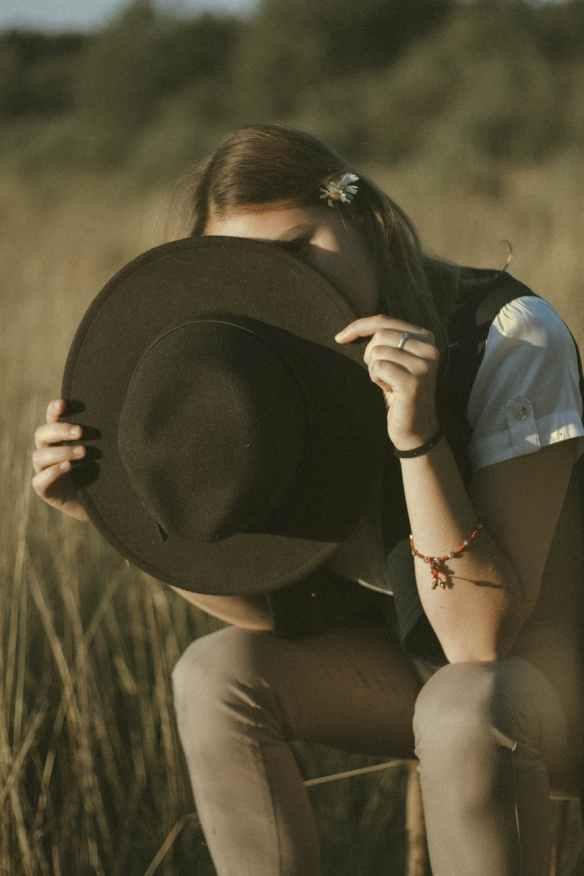 unrecognizable female hiding face behind hat