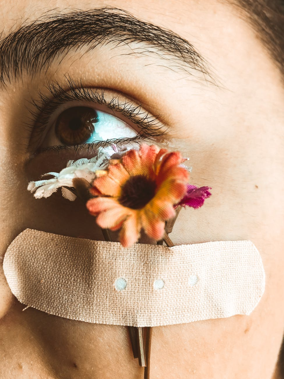 woman with flowers glued to face