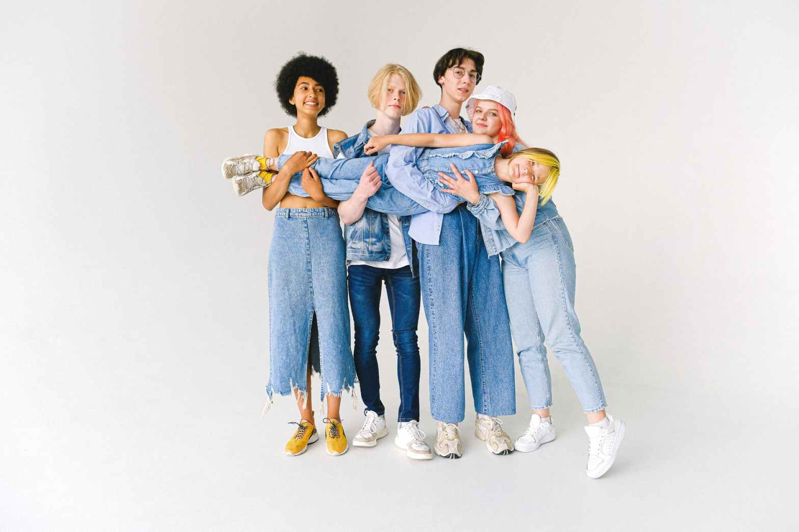 multiracial group of friends carrying child on hands