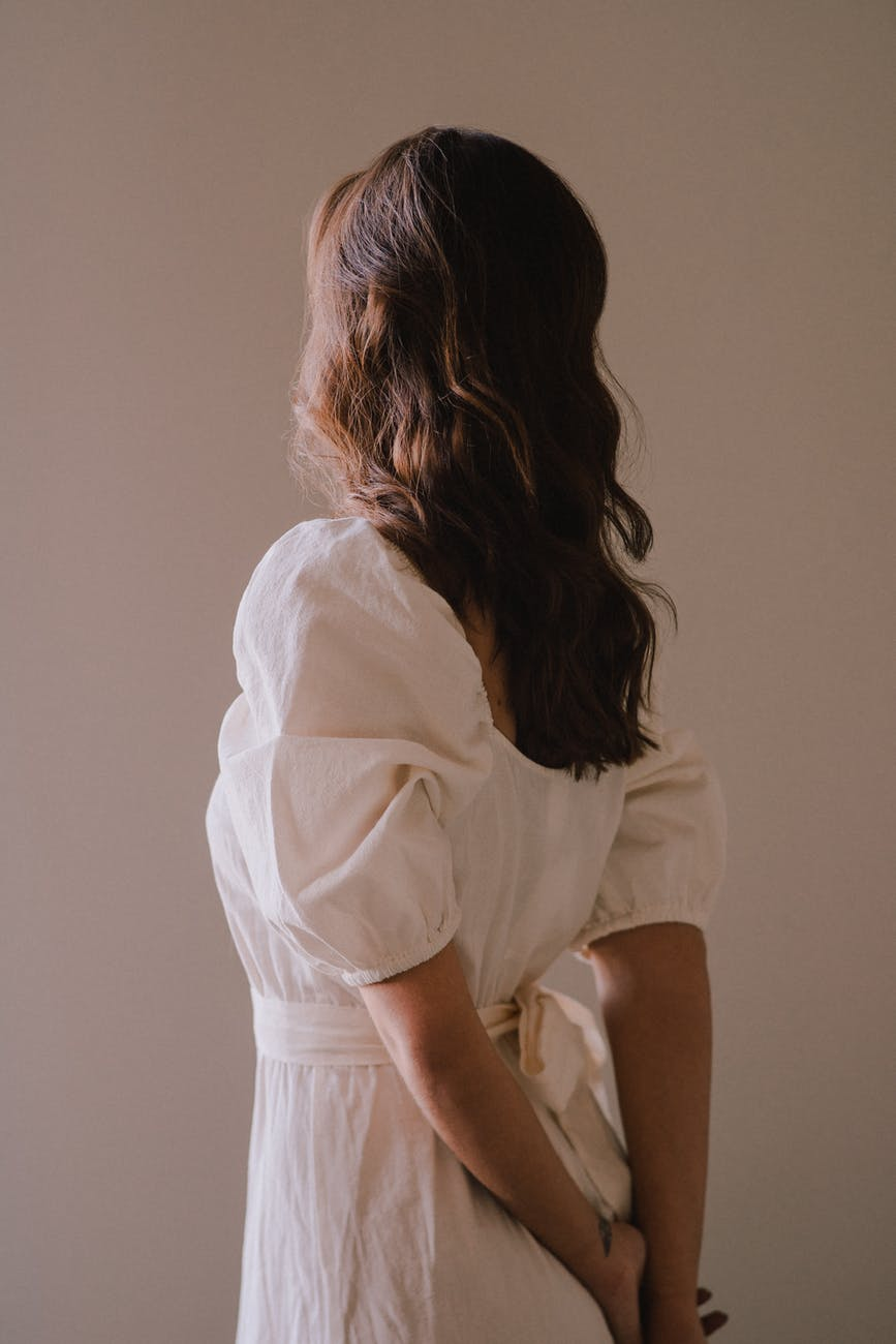 faceless stylish woman standing with hands behind back