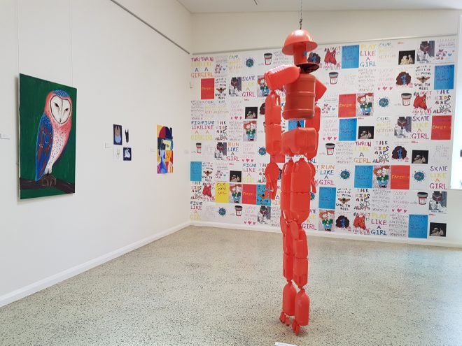 Red sculpture made from plastic bottles, and posters made by participants of the Messengers program.