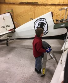 Small boy with a ladder beside small airplane.
