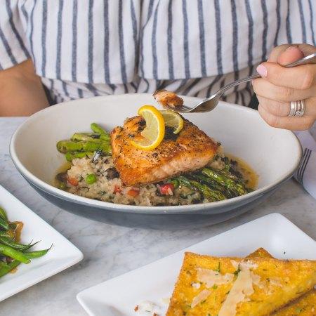 woman eating fish at table