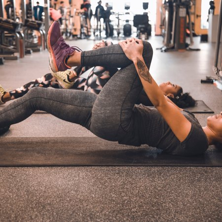 HIIT workout girl stretching her leg on a mat
