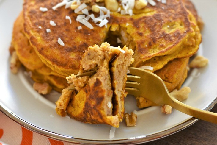 Pumpkin pancake on a plate with a bite on a fork