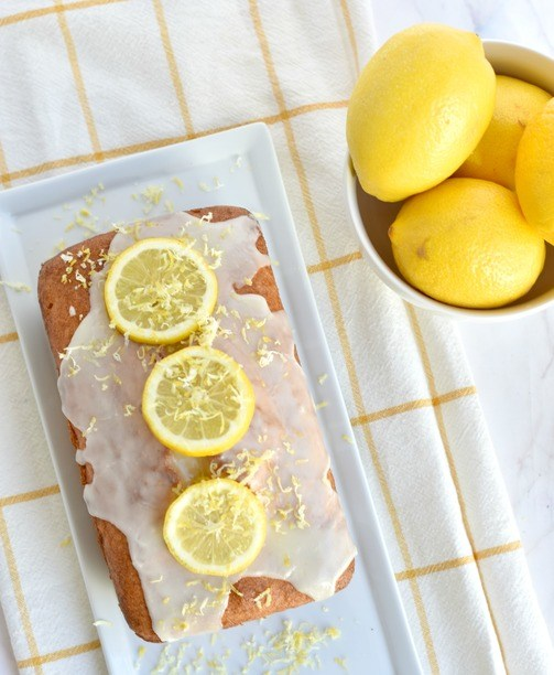 gltuen free lemon loaf on a plate with lemons