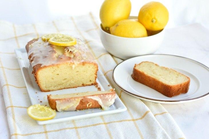 Sliced gltuen free lemon loaf on a plate with lemons