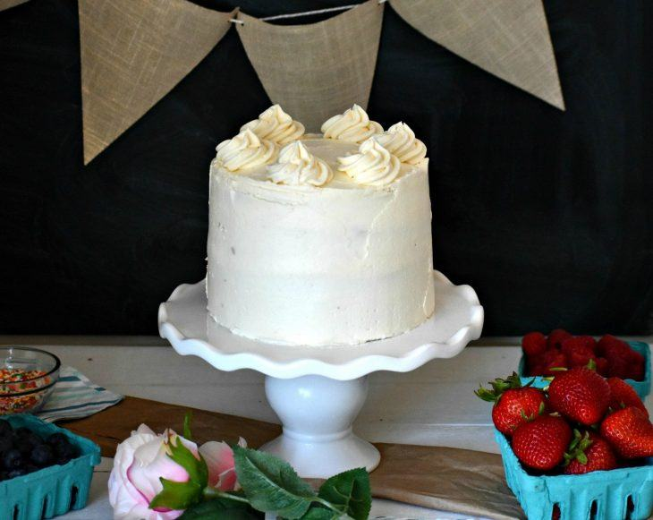 Vanilla Cake on a cake plate surrounded by berries