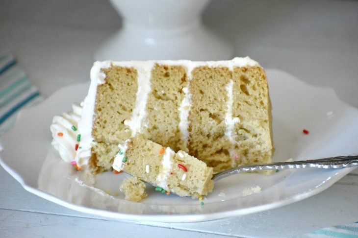 Slice of vanilla cake on a plate with a bite on a fork