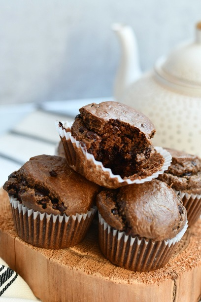 Chocolate Muffins stacked with one on top with a bite taken out