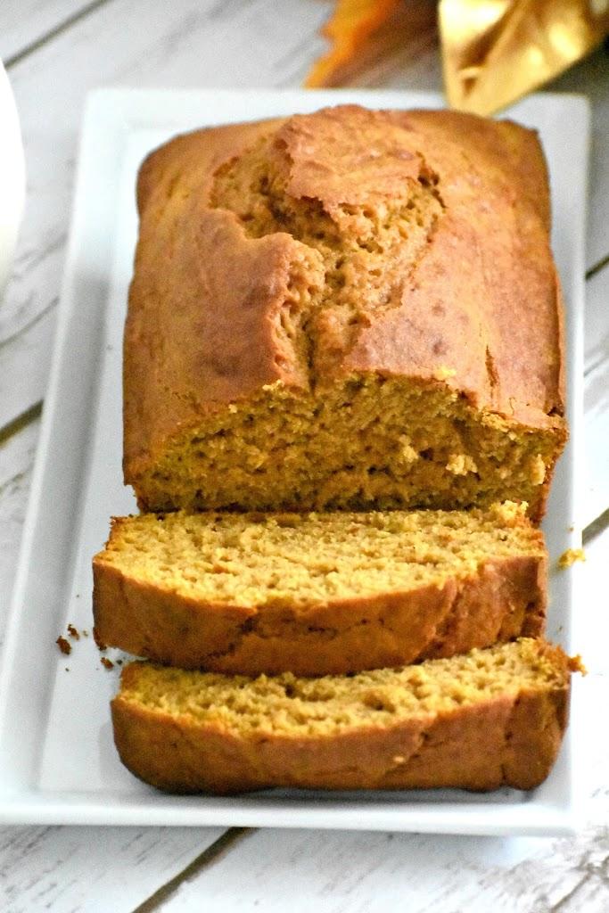 Loaf of gluten free pumpkin bread on a plate sliced