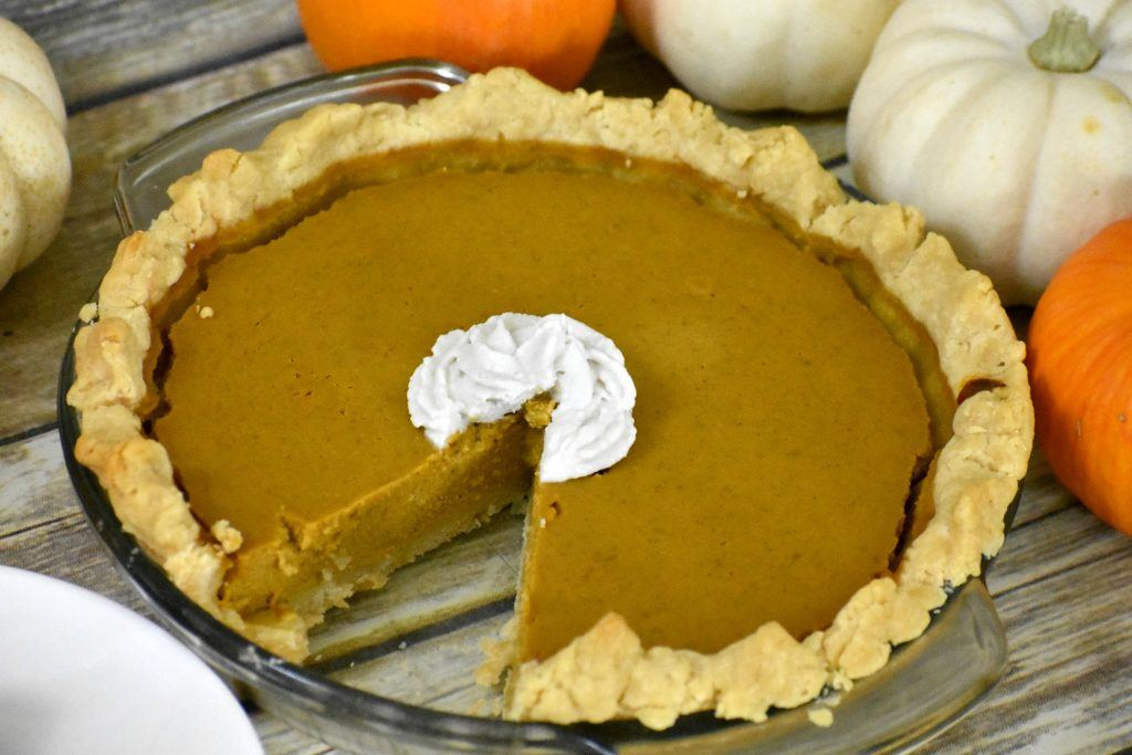 Easy gluten free pumpkin pie on a table with a slice missing