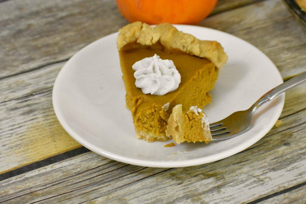 slice of gluten free pumpkin pie on a plate with a bite on a fork