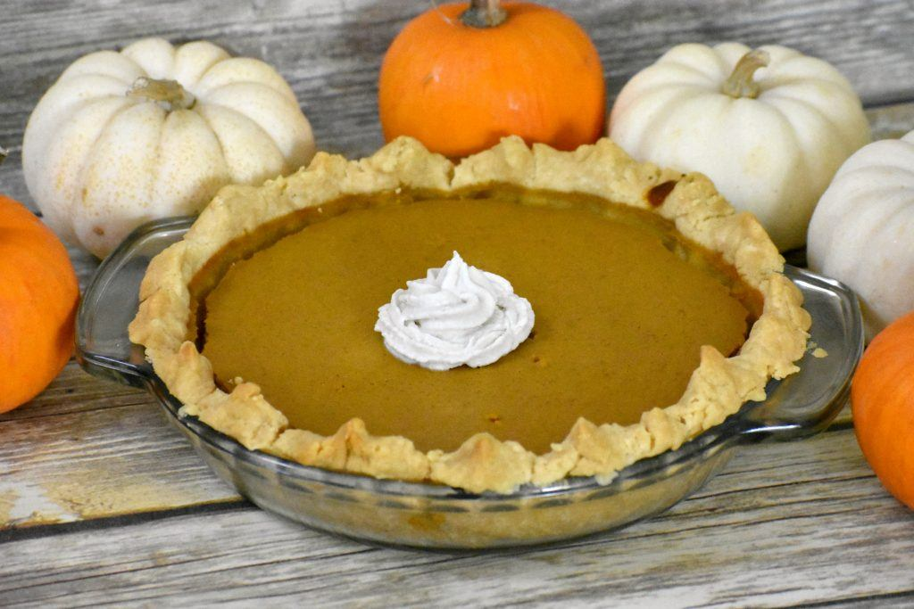 easy gluten free pumpkin pie on table surrounded by pumpkins