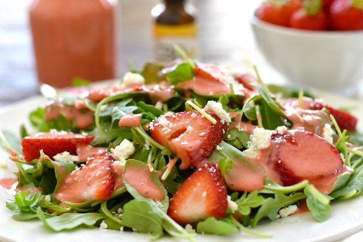 Strawberry Arugula Salad on a white plate.