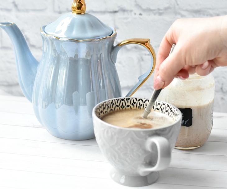 Stirring coffee creamer into cup