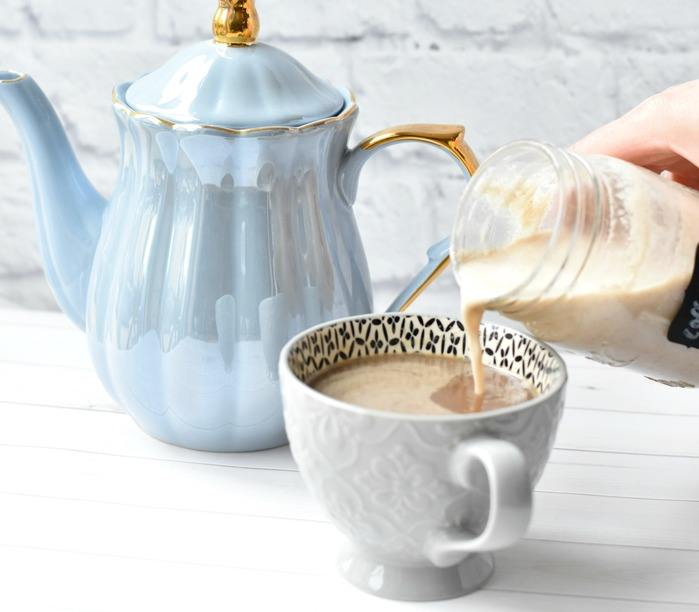 Pouring Coffee Creamer into cup