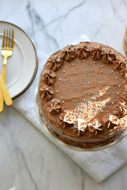 Paleo chocolate cake on a table with plates and forks