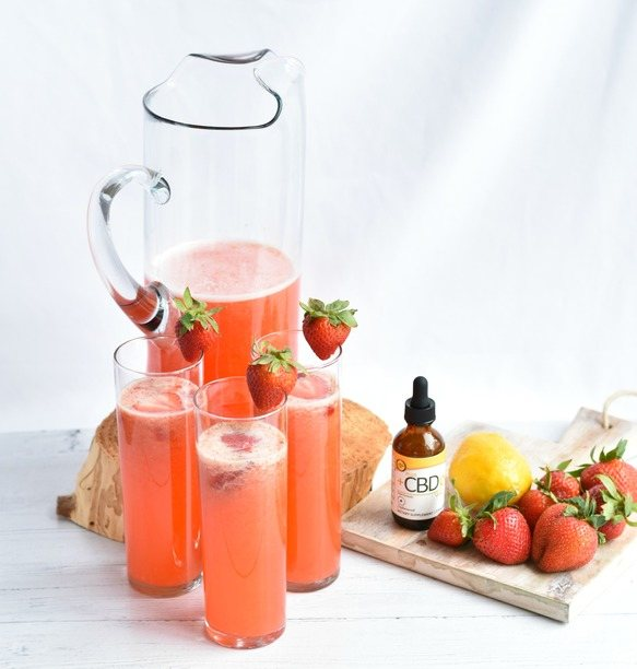 cbd strawberry lemonade on a table in glasses with fruit and cbd drops