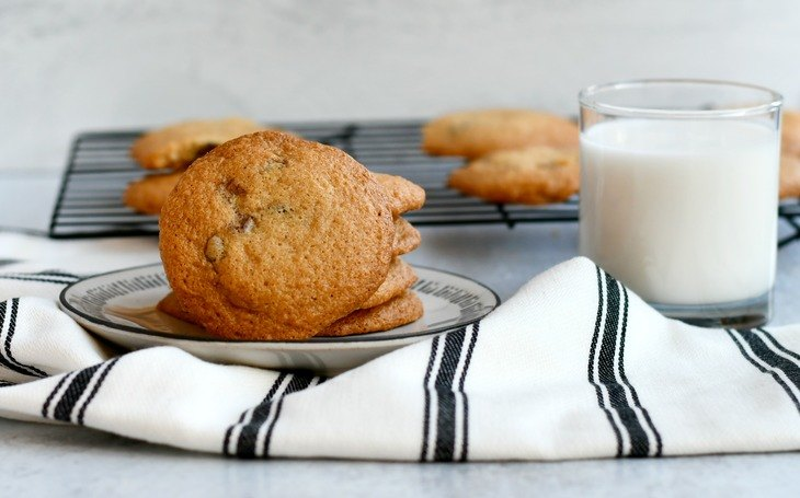 gluten free chocolate chip cookies on a plate with a towel and cup of milk